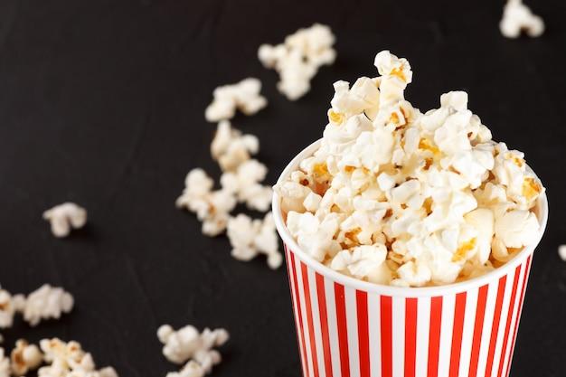Banner orizzontale di popcorn. tazza e noccioli di carta spogliati rossi che si trovano sulla priorità bassa scura. Foto Premium