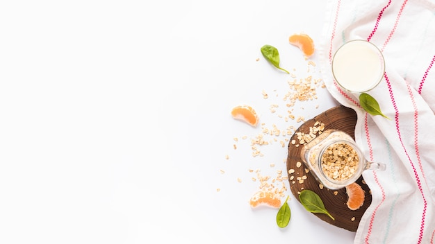 Barattolo di avena; foglie di basilico; fette d'arancia; latte e tovagliolo su sfondo bianco Foto Gratuite
