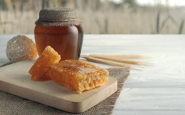 Barattolo di miele e barattolo di miele sul tavolo e campo di grano in background Foto Premium