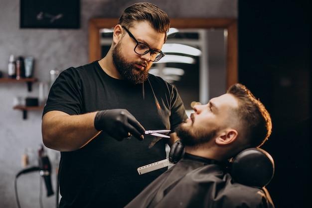 Barba di taglio uomo bello in un salone del negozio di barbiere Foto Gratuite