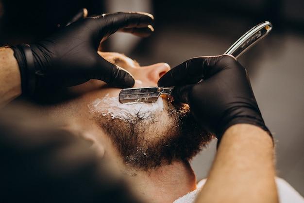 Barba di taglio uomo bello in un salone di barbiere Foto Gratuite