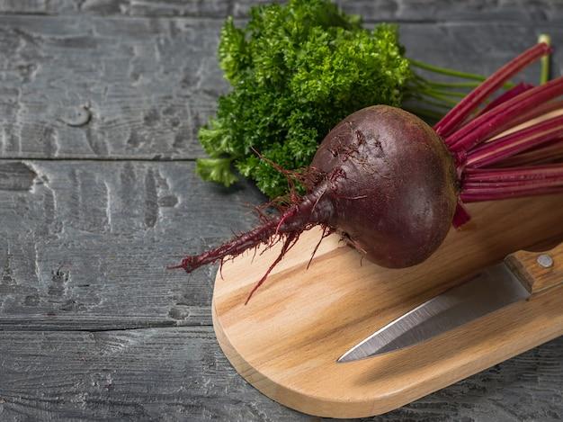 Barbabietole rosse fresche con un coltello e un mazzo di prezzemolo sul tagliere. Foto Premium