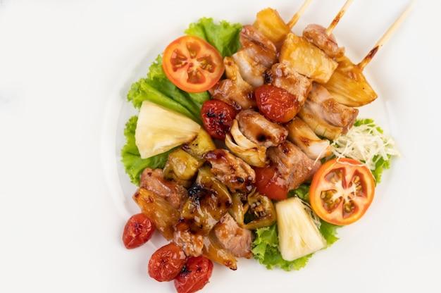 Barbecue con una varietà di carni, completo di pomodori e peperoni su un piatto bianco. Foto Gratuite