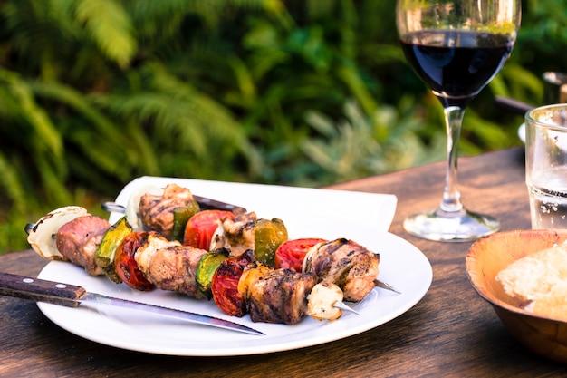 Barbecue di carne e verdure che serve a tavola e bicchiere di vino Foto Gratuite