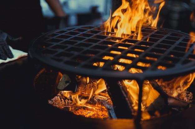 Barbecue, primo piano. cucinando professionalmente il cibo su un fuoco aperto su una griglia in ghisa. Foto Gratuite