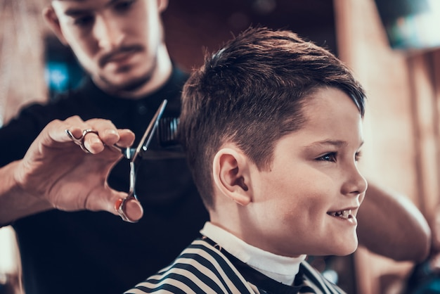 Barber clips handsome kid sides with scissors Foto Premium