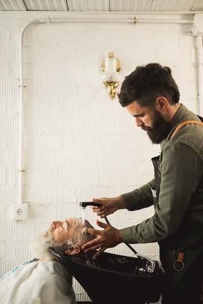 Barbiere adulto che lava i capelli del vecchio su risucchio Foto Gratuite
