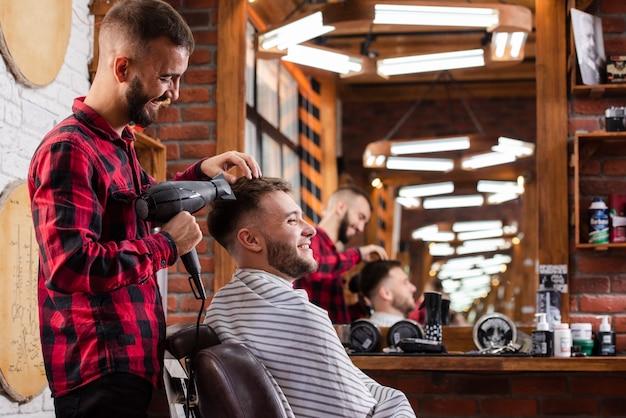 Barbiere asciuga i capelli dei clienti mentre sorride Foto Gratuite