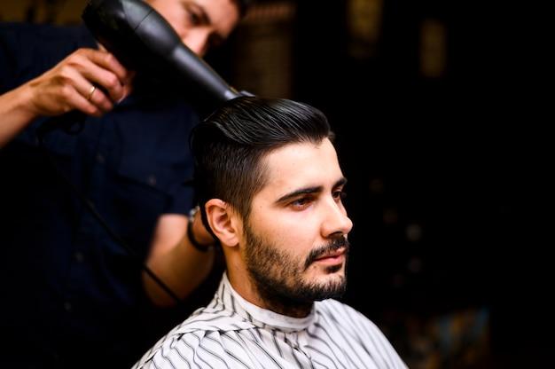 Barbiere che asciugava i capelli del suo cliente Foto Gratuite