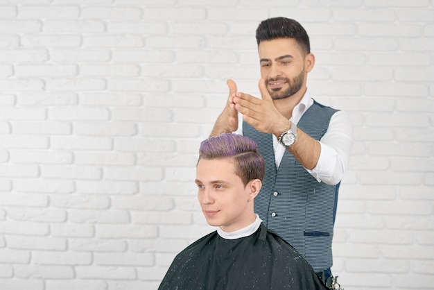 Barbiere che fa i capelli lilla che tonificano per il giovane cliente. Foto Premium
