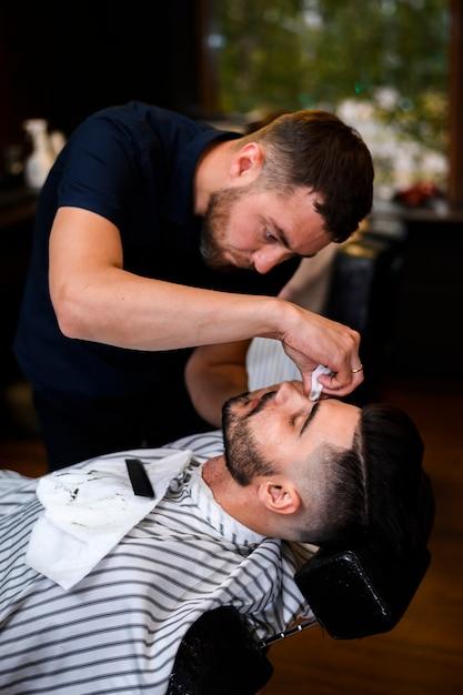 Barbiere che taglia la barba di un uomo Foto Gratuite