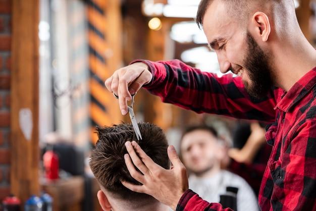 Barbiere con le forbici per fare una pettinatura Foto Gratuite