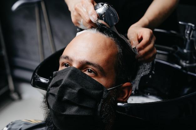 Barbiere donna che lava i capelli a un uomo barbuto in ...