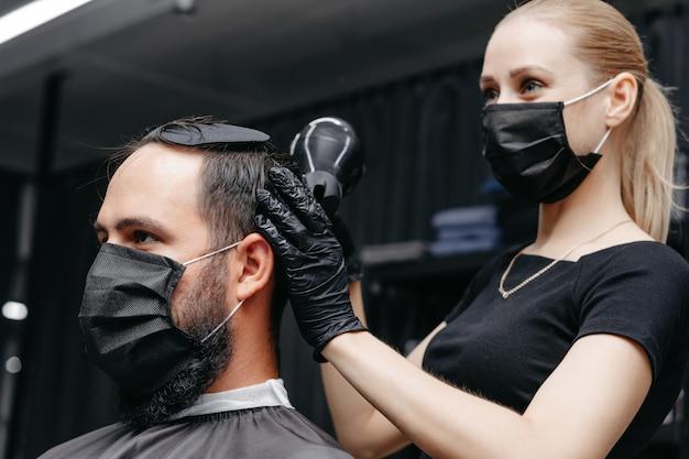 Barbiere donna taglio di capelli a un uomo barbuto in ...