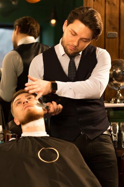 Barbiere professionista che lavora nel suo barbiere Foto Premium