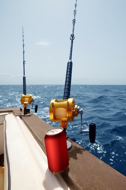 Barca da pesca con canna e mulinelli d'oro, bevanda africana Foto Premium