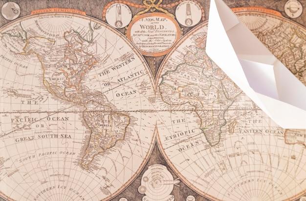 Barca di carta di vista superiore sulla mappa del vecchio mondo Foto Gratuite