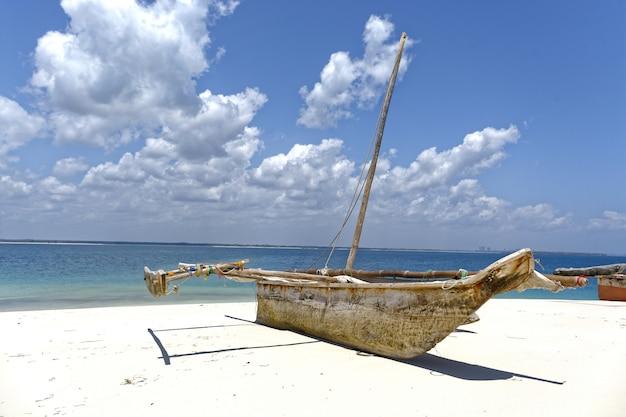 Barca sulla riva vicino al mare in una giornata di sole con cielo nuvoloso in background Foto Gratuite