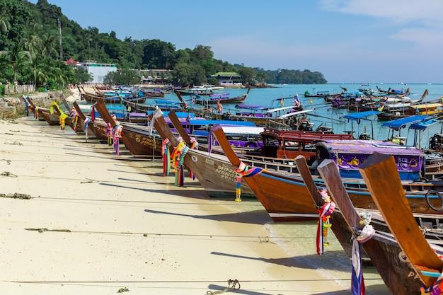 Barche di legno tradizionali di pesca tailandese avvolte con nastri colorati. Foto Premium