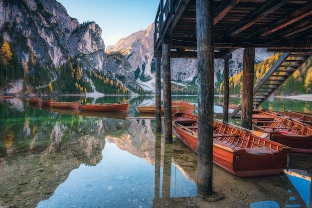 Barche di legno vicino alla casa nel lago braies ad alba in autunno Foto Premium