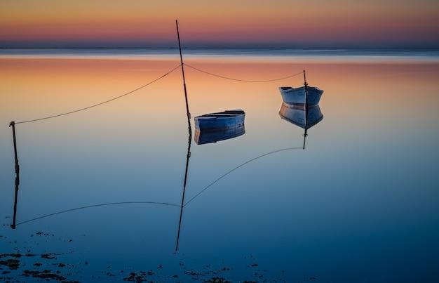 Barche galleggianti ob l'acqua sotto il cielo colorato Foto Gratuite
