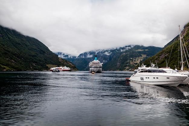 Barche ormeggiate e crociera ormeggiata sul lago idilliaco Foto Gratuite