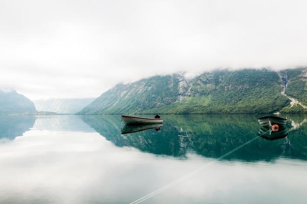 Barche solitarie in un lago calmo con montagna nebbiosa a sfondo Foto Gratuite