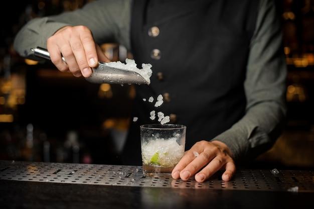 Barista aggiungendo cubetti di ghiaccio nel bicchiere da cocktail. processo di preparazione del cocktail caipirinha Foto Premium