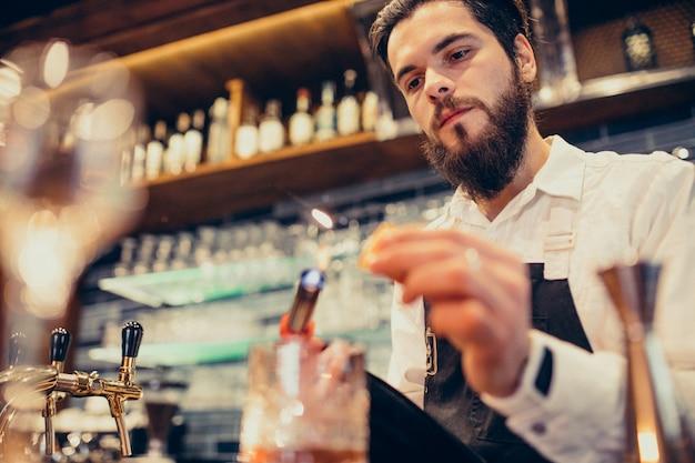 Barista bello che fa bere e cocktail ad un contatore Foto Gratuite