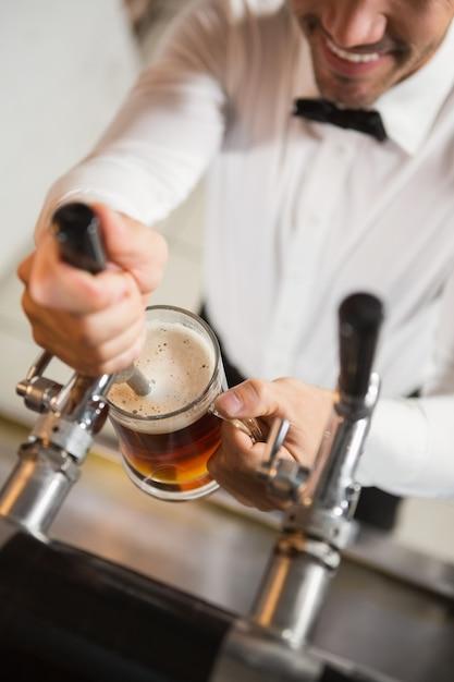 Barista bello che versa una pinta di birra Foto Premium