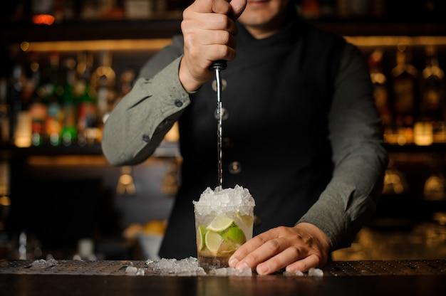 Barista che versa cachaca nel bicchiere da cocktail. processo di preparazione del cocktail caipirinha Foto Premium