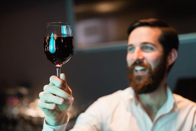 Barista guardando un bicchiere di vino rosso Foto Gratuite