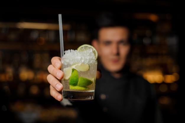 Barista in possesso di un bicchiere con un mojito fresco Foto Premium