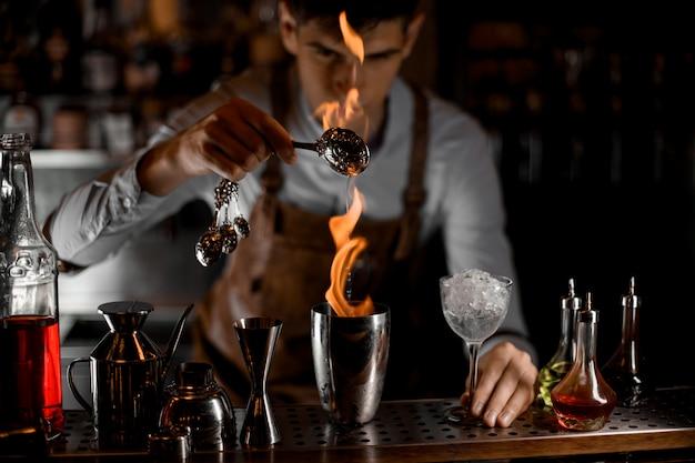 Barista maschio attraente che versa un'essenza dal cucchiaio nella fiamma allo shaker d'acciaio Foto Premium