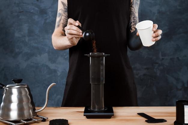 Barista maschio che prepara caffè. aeropress metodo alternativo. Foto Gratuite