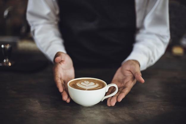Barista maschio che prepara caffè per il cliente in caffetteria. proprietario del bar che serve un cliente al bar. Foto Premium