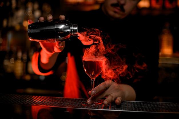 Barista maschio che versa un fumo nel bicchiere da cocktail dall'agitatore d'acciaio Foto Premium
