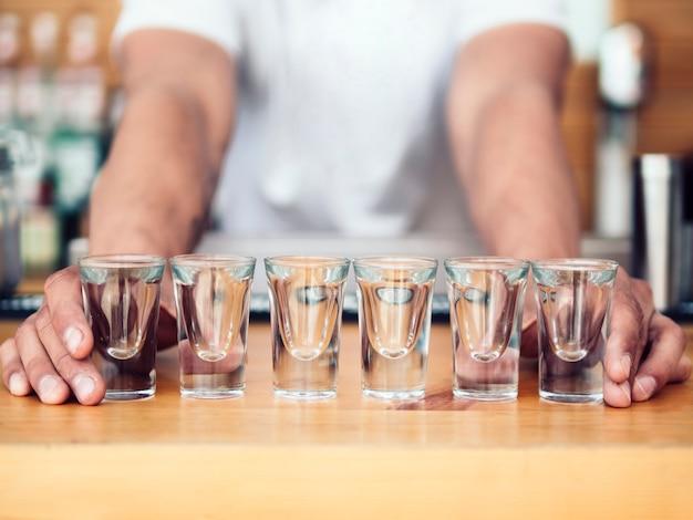 Barista posizionando la linea di bicchierini sul bancone Foto Gratuite