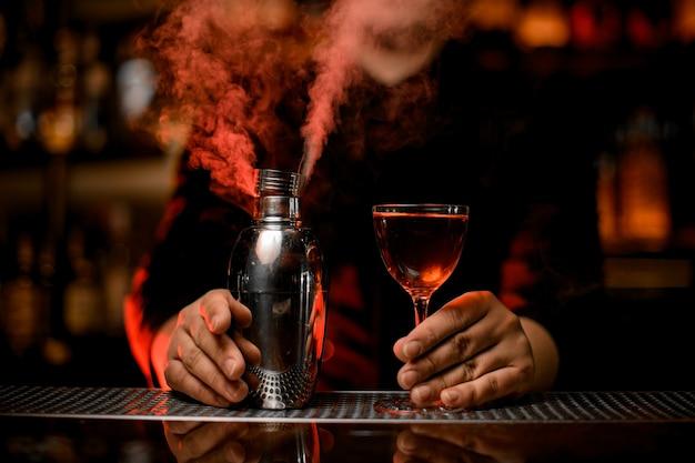 Barista professionista che tiene un cocktail nel bicchiere e shaker fumoso Foto Premium