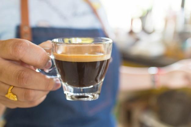 Barista professionista che tiene una tazza di caffè calda nella caffetteria. Foto Premium