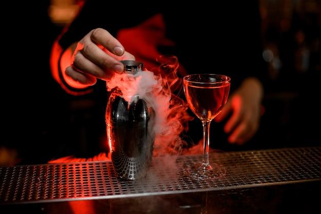 Barista professionista in possesso di un tappo dell'agitatore fumoso vicino al cocktail nel bicchiere Foto Premium