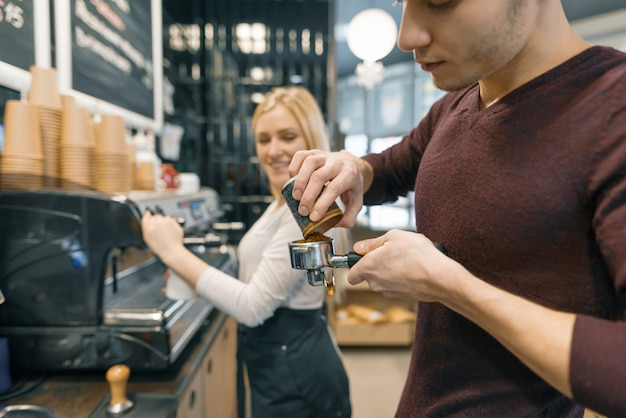 Barista uomo e donna che fanno caffè, coppia di giovani che lavorano in caffetteria. Foto Premium