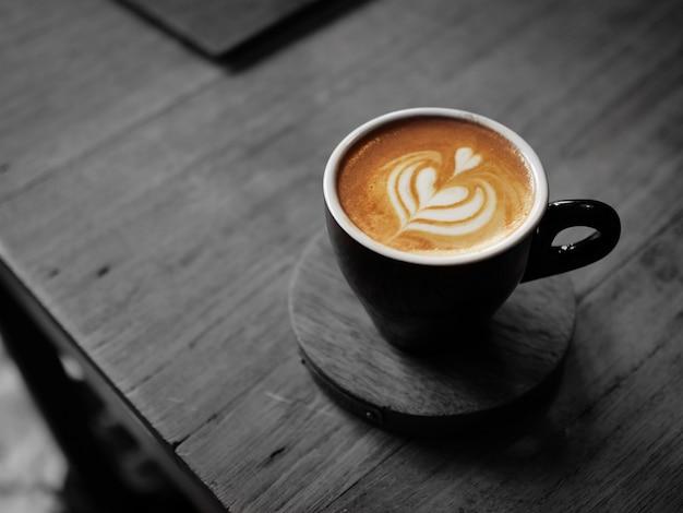 Barista versando latte alla tazza di caffè latte art Foto Premium