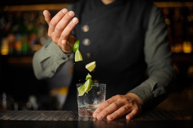 Barman aggiungendo fette di lime nel bicchiere Foto Premium