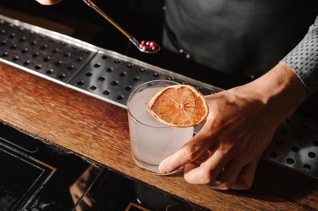 Barman che decora un bicchiere pieno di una bevanda alcolica torbida Foto Premium