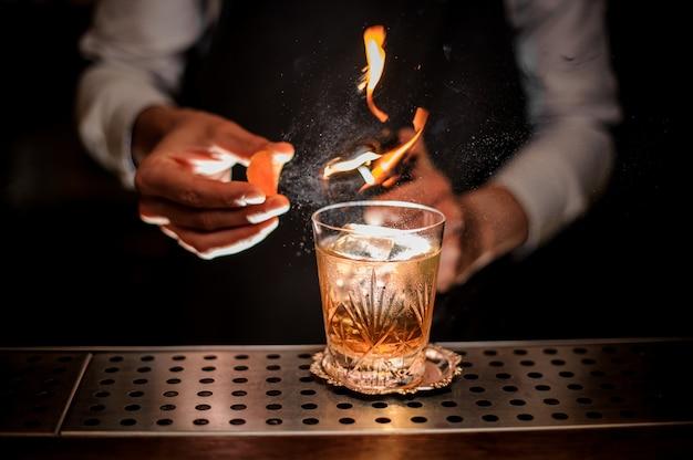 Barman che produce un fresco e gustoso cocktail vecchio stile con buccia d'arancia e nota di fumo Foto Premium