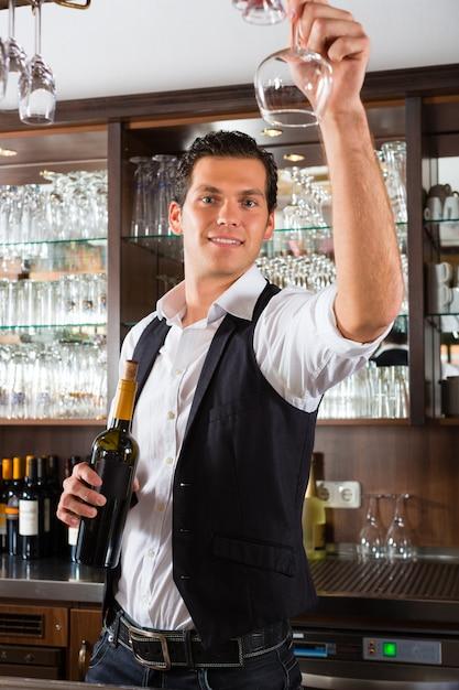 Barman in piedi dietro la barra con il vino Foto Premium