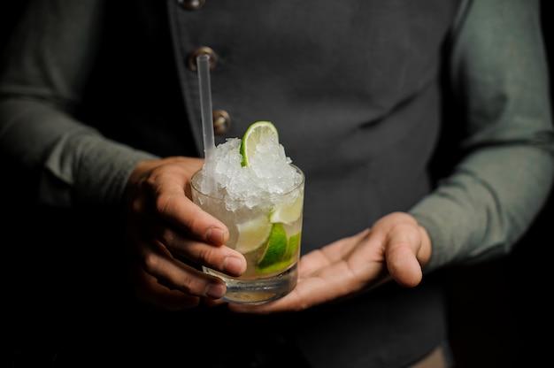 Barman in possesso di un bicchiere con un mojito fresco Foto Premium