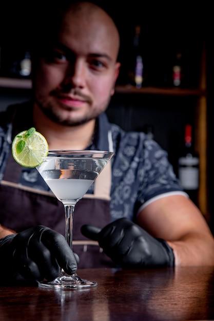Barman offre cocktail al cliente al bar del ristorante. benvenuto Foto Premium