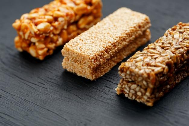 Barretta ai cereali con arachidi, sesamo e semi di girasole su un tagliere su un tavolo di pietra scura. vista dall'alto tre barre assortite Foto Premium